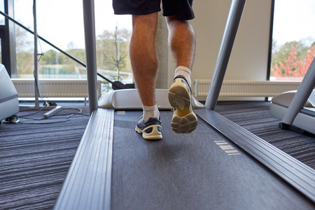 man legs: sport, fitness, lifestyle, technology and people concept - close up of man legs walking on treadmill in gym from back