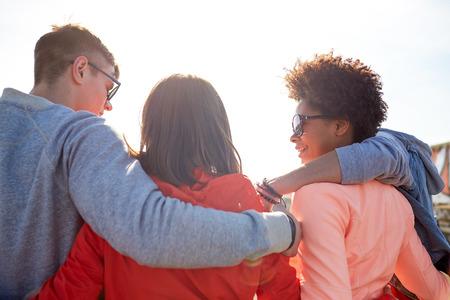 familia abrazo: turismo, viaje, gente, ocio y concepto de adolescente - grupo de amigos felices que abrazan y que hablan en calle de la ciudad de la parte posterior