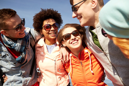 happy teens: tourism, travel, people, leisure and teenage concept - group of happy friends in sunglasses hugging and laughing on city street