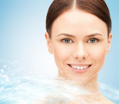 pulizia viso: bellezza, la gente, la freschezza, la purezza e concetto di salute - volto della giovane e bella donna e spruzzi d'acqua su sfondo blu