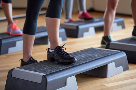 aerobics class: fitness, sport, people, step aerobics and lifestyle concept - close up of women legs exercising with steppers in gym