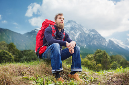 sitting on the ground: adventure, travel, tourism, hike and people concept - smiling man with red backpack sitting on ground over alpine mountains background Stock Photo
