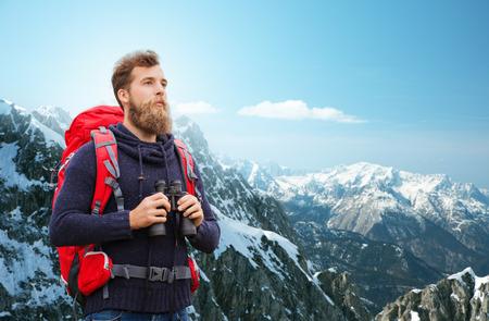 aventura: aventura, viajes, turismo, ir de excursión y la gente concepto - hombre con mochila roja y binocular sobre fondo de las montañas alpinas Foto de archivo