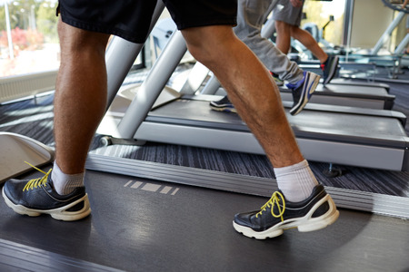 body parts man: sport, fitness, lifestyle, technology and people concept - close up of men legs walking on treadmills in gym