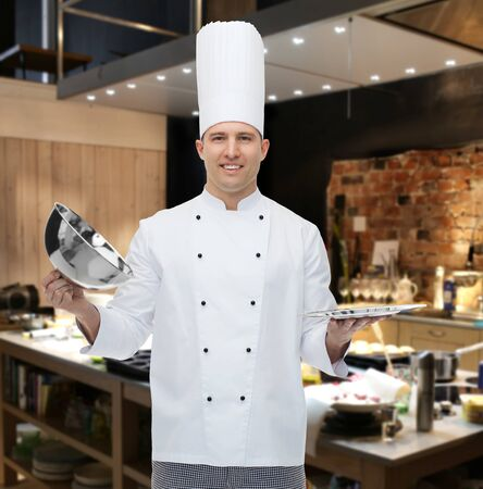 cloche: cooking, profession and people concept - happy male chef cook opening cloche cover over restaurant kitchen