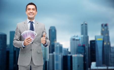 eur: business, people and finances concept - smiling businessman with european money showing thumbs up over city background