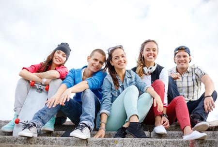 夏休みと 10 代のコンセプト - 外にぶら下がって笑顔ティーンエイ ジャーのグループ