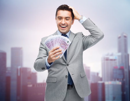 eur: business, people and finances concept - happy laughing businessman with euro money over city background