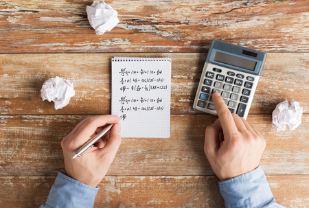 algebraic: business, education, people and technology concept - close up of male hands with calculator, cramped paper wads and notebook solving mathematical task or equation