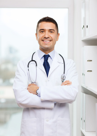 healthcare, profession, people and medicine concept - smiling male doctor in white coat at medical office Фото со стока
