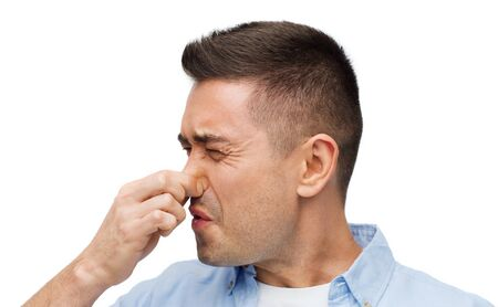 unpleasant: emotions, gesture and people concept - man wrying of unpleasant smell and closing his nose