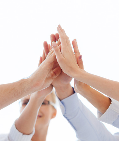 5: success and winning concept - happy business team giving high five in office