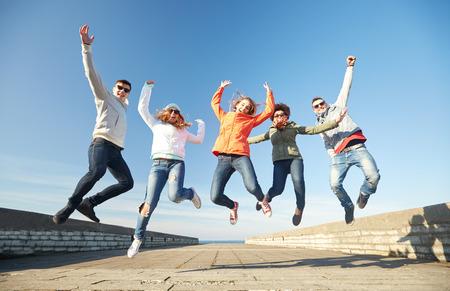 Tourisme, Voyage, les gens, les loisirs et le concept adolescente - groupe d'amis heureux lunettes de soleil étreignant et rire sur rue de la ville