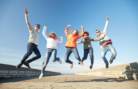 personas saltando: turismo, viaje, gente, ocio y concepto de adolescente - grupo de amigos felices en gafas de sol que abrazan y ríen en calle de la ciudad