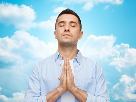 dedication: faith in god, religion and people concept - happy man with closed eyes praying over blue sky with clouds background Stock Photo