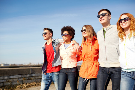 tourism, travel, people and leisure concept - group of happy teenage friends walking along city street Stock Photo