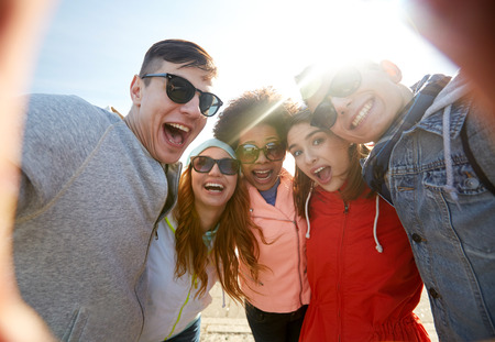 laughing girl: tourism, travel, people, leisure and technology concept - group of happy laughing teenage friends taking selfie outdoors