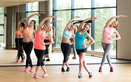 피트니스, 스포츠, 교육, 헬스 클럽 및 생활 양식 개념 - 체육관에서 일하는 여성 그룹