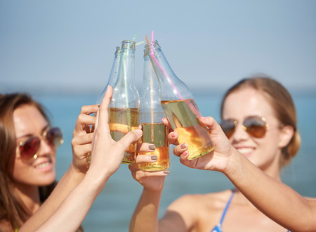 summer vacation, holidays, party, travel and people concept - close up of happy young women with drinks clinking bottles on beach Stock Photo