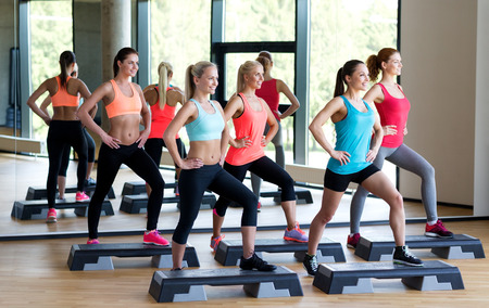 women working out: fitness, sport, training, gym and lifestyle concept - group of women working out with steppers in gym Stock Photo