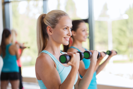 fitness, sport, people and lifestyle concept - group of women exercising with dumbbells in gym