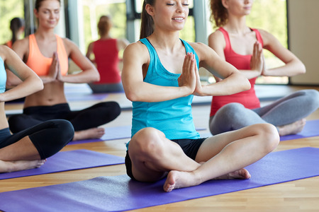 sitting meditation: sport, meditation, yoga, people and lifestyle concept - group of happy women meditating on mat in gym