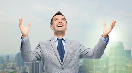 people looking up: business, people and success concept - happy businessman in suit with raised hands laughing and looking up over city background