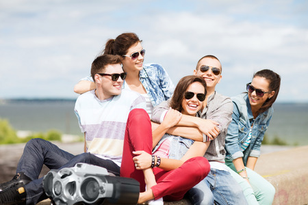chilling out: summer holidays and teenage concept - group of teenagers hanging out