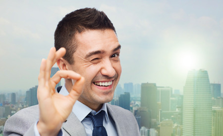 ok sign: business, people, gesture and success concept - happy smiling businessman in suit showing ok hand sign over city background