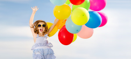 birthday party kids: summer holidays, celebration, children and people concept - happy jumping girl with colorful balloons outdoors Stock Photo