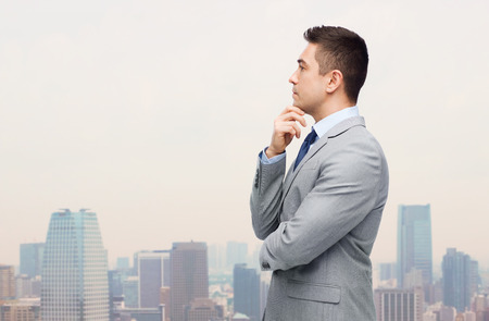 decision making: business and people concept - thinking businessman in suit making decision over city background Stock Photo
