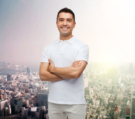 mani incrociate: happiness and people concept - smiling man in white t-shirt with crossed arms over city background