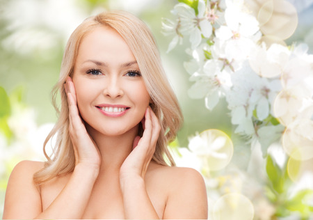 skin care: beauty, people, summer, spring and health concept - beautiful young woman touching her face over green blooming garden background
