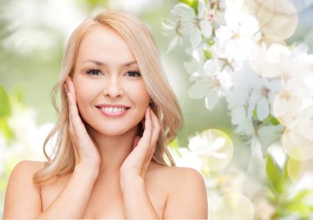 piel humana: belleza, gente, verano, primavera y el concepto de salud - mujer hermosa joven tocando la cara sobre el verde florece el fondo del jard�n Foto de archivo