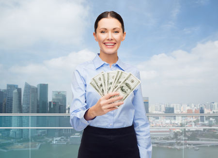 cash money: business and money concept - young businesswoman with dollar cash money over city background Stock Photo