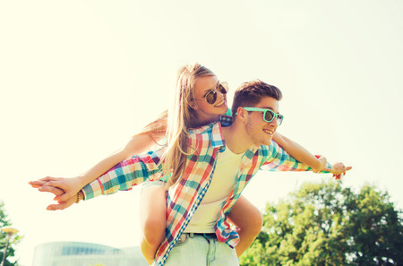 best friends: holidays, vacation, love and friendship concept - smiling couple having fun in park Stock Photo