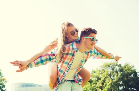amicizia: vacanze, vacanza, amore e amicizia concetto - sorridente coppia divertirsi nel parco