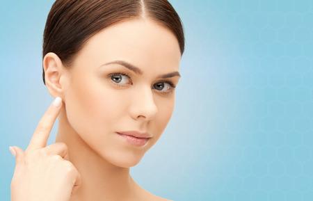 人々、美しさ、公聴会、医療コンセプト - 青い背景に彼女の耳に触れる美しい女性の顔 写真素材