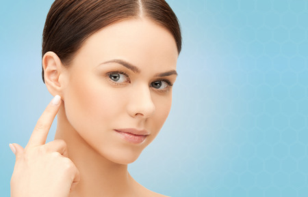 piercing: people, beauty, hearing and healthcare concept - face of beautiful woman touching her ear over blue background