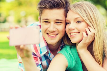 teen couple: vacation, holidays, technology and friendship concept - smiling couple lying on blanket and making selfie with smartphone in park