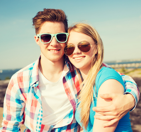 holidays, vacation, love and friendship concept - smiling couple having fun outdoors photo