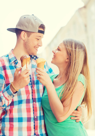 teen couple: summer, vacation, love and friendship concept - smiling couple with ice-cream looking to each other in city