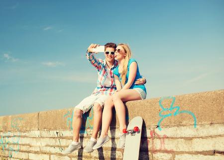 haciendo el amor: días de fiesta, vacaciones, el amor y la amistad concepto - sonriente pareja que se divierten al aire libre Foto de archivo