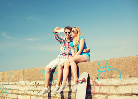making fun: holidays, vacation, love and friendship concept - smiling couple having fun outdoors Stock Photo