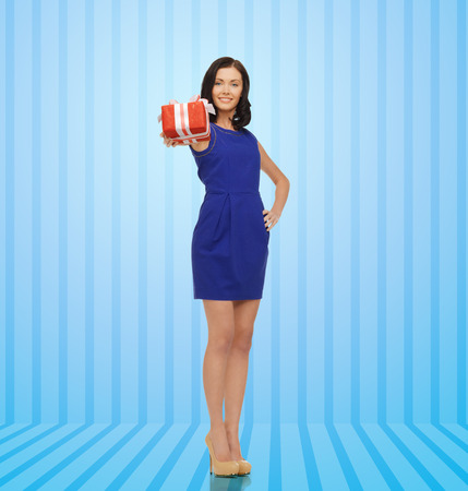 people, holidays, greetings, gifts and shopping concept - happy young woman in blue dress with present over blue striped background photo
