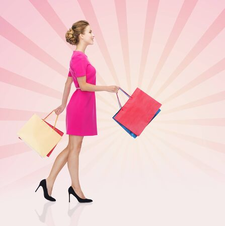 consumerism: people, retail, sale and consumerism concept - happy young woman in dress with red shopping bags sign over pink burst rays background
