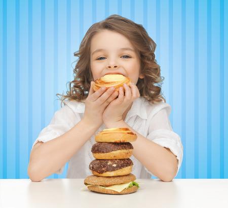 人・栄養、小児保健の概念 - 青い縞模様の背景の上にジャンク フードを食べて幸せな少女