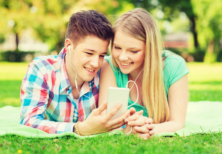 making music: vacation, holidays, technology and friendship concept - smiling couple with smartphone and earphones making selfie in park Stock Photo