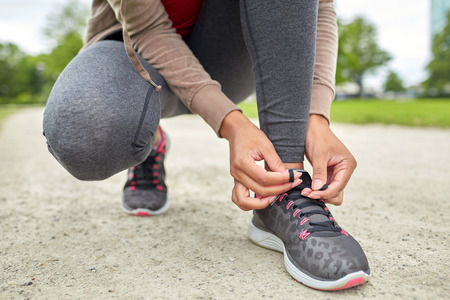 sport, fitness, people and lifestyle concept - close up of woman tying shoelaces outdoors Stock Photo