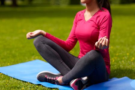 mujer meditando: deporte, meditación, yoga, fitness y la gente concepto - cerca de la mujer meditando en la estera en el parque